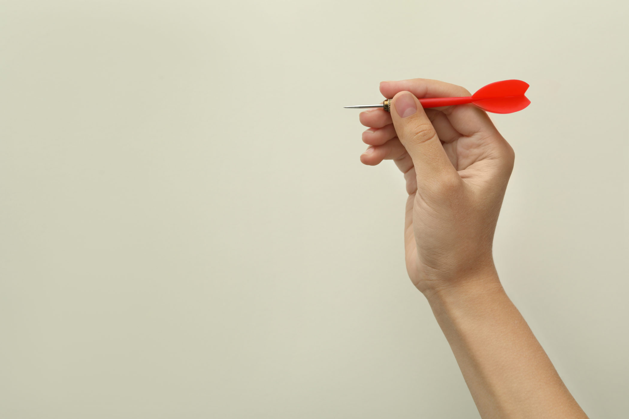 Woman holding red dart on light background, closeup. Space for text