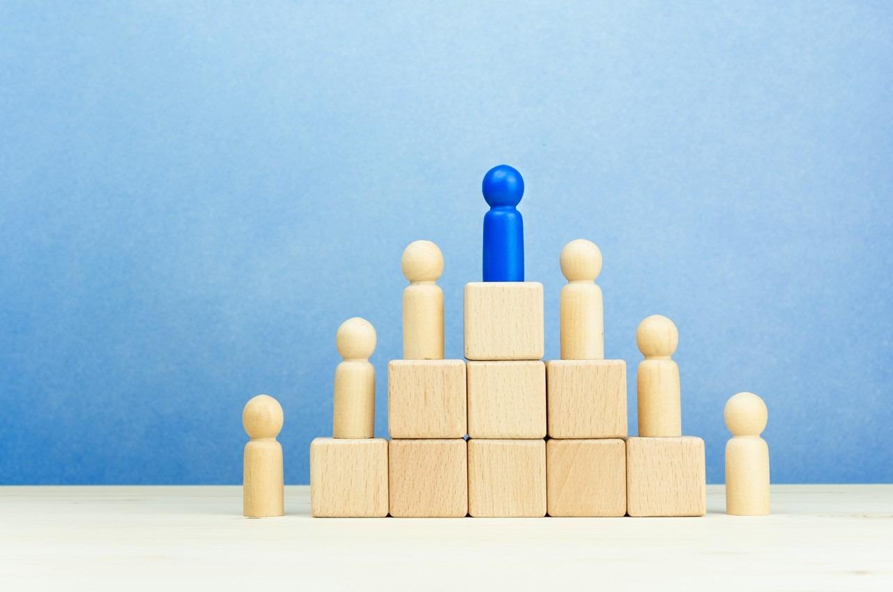 Piramida z pionkami - postaciami ustawionymi na jej stopniach. Na najwyższym stoi lider