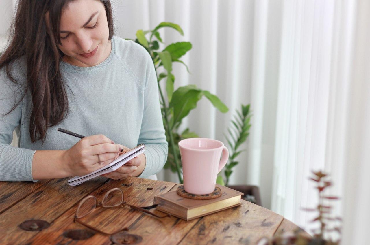 Kobieta siedząca przy stole i robiąca notatki